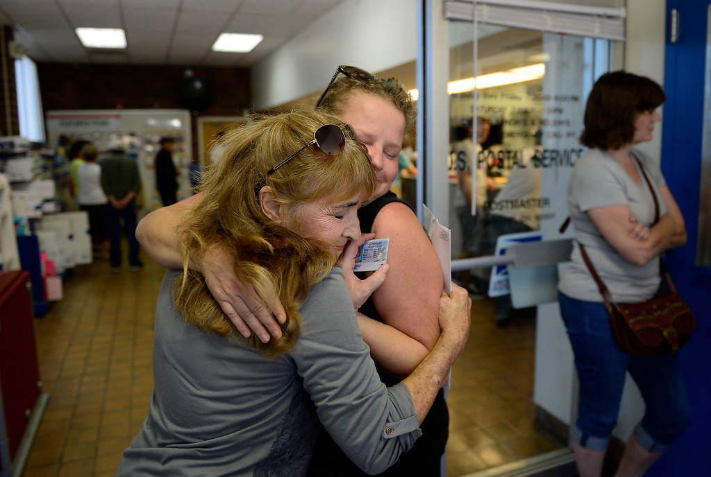 Description of . Lyons-area residents Aleta Hammonds, left, and Jenna Brink embrace after sharing stories of their flood experiences while they were getting their mail at the Longmont Post Office Tuesday, Sept. 17, 2013. Both lost their homes in the flood. (Lewis Geyer/Times-Call)