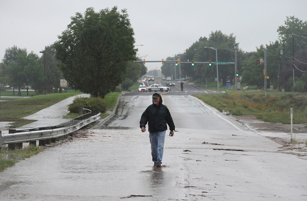 Description of . Wayne Hoeben walks through the water flowing over Pike Road 10:10 a.m. Thursday Sept. 12, 2013. (Lewis Geyer/Times-Call)