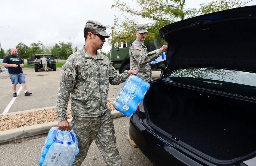 Description of . U.S. Army National Guard P.F.C. Jordan Gray loads bottled water into a weld county residents car, Monday, Sept. 16, 2013, in Del Camino.