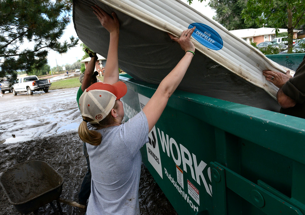 Description of . Hannah Brinkman helps toss a mattress into a dumpster at 108 Gay St., in the Bohn Park neighborhood, Saturday morning, Sept. 14, 2013. (Lewis Geyer/Times-Call)