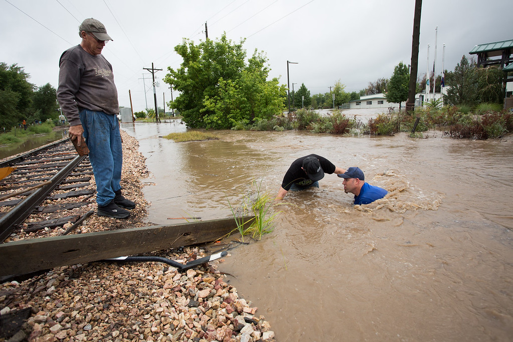 Description of . Three men work to plug a culvert under the train tracks near Sunset St. in a vain attempt to stem the flow as the St. Vrain river floods after days of torrential rains, on Thursday Sept. 12, 2013 in Longmont, Colo.