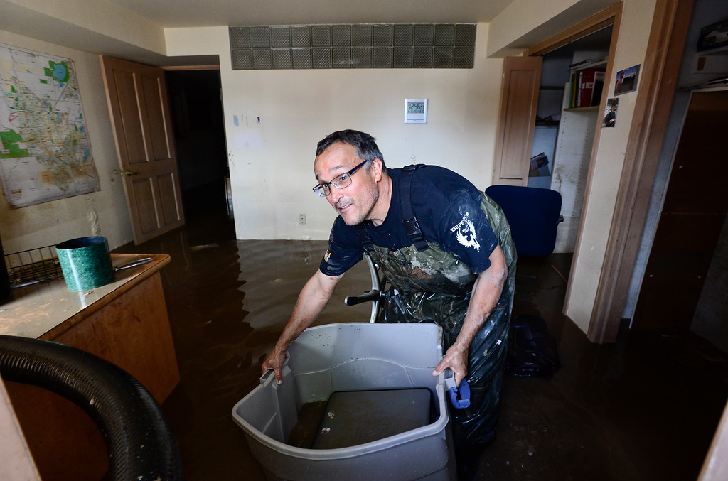Description of . Ray Hummer, of Longmont, picks up a bin containing a flooded computer from his basement on Twin Peaks Circle, Monday, Sept. 16, 2013, in Longmont.