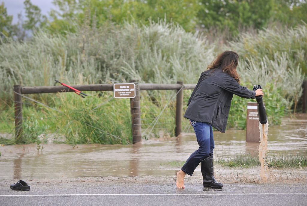 Description of . Caren Tarantino, of Hygiene, dumps water out of her boots after working to rescue a pair of horses near Hygiene Road and North 75th, Thursday, Sept. 12, 2013, near Hygiene.