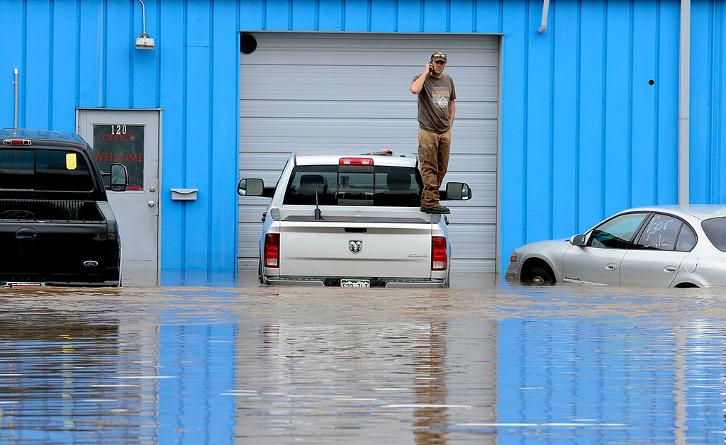 Description of . A man stands on a pickup outside AP Automotive along Price Road Thursday Sept. 12, 2013. He was soon after rescued by Longmont firefighters in a large forklift. (Lewis Geyer/Times-Call)