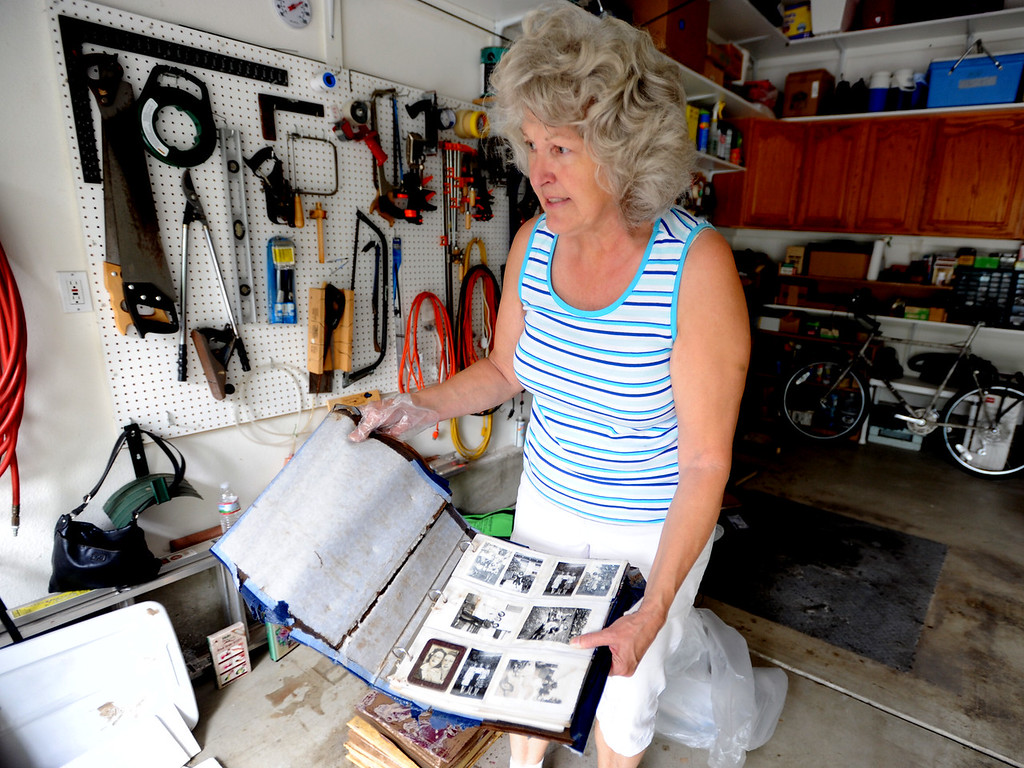 Description of . Rose Marie Rempel holds an old photo album that has water damage from the flooding on September 14, 2013. She lives in the Champion neighborhood in Longmont, Colorado.