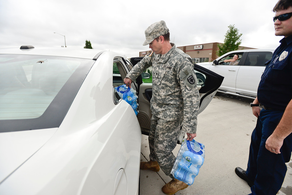Description of . U.S. Army National Guard Spc. Jeremiah Anderson helps to load bottled water into a car, Monday, Sept. 16, 2013, in Del Camino.