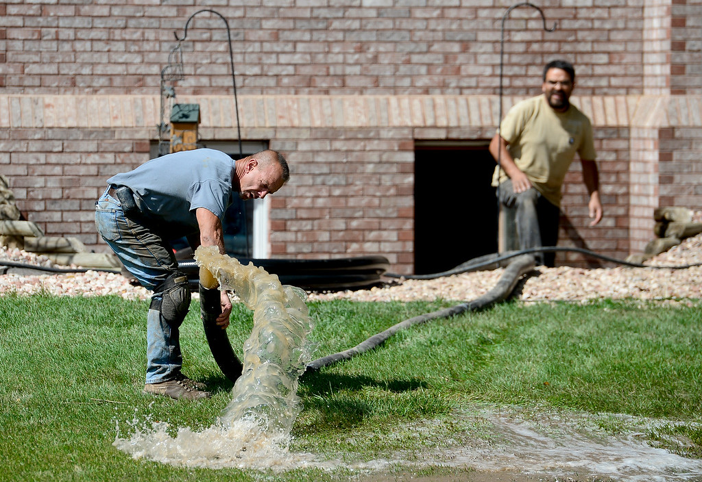 Description of . Robert Pandolfi, of Longmont, works to move a hose from a pump in a basement on Twin Peaks Circle, Monday, Sept. 16, 2013, in Longmont.