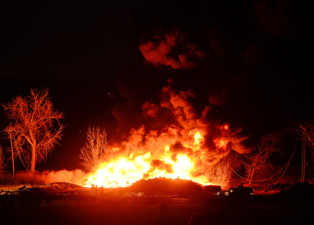 Description of . Flames from a railroad tie fire are seen, Wednesday, April 16, 2014, in Longmont. (Matthew Jonas/Longmont Times-Call)