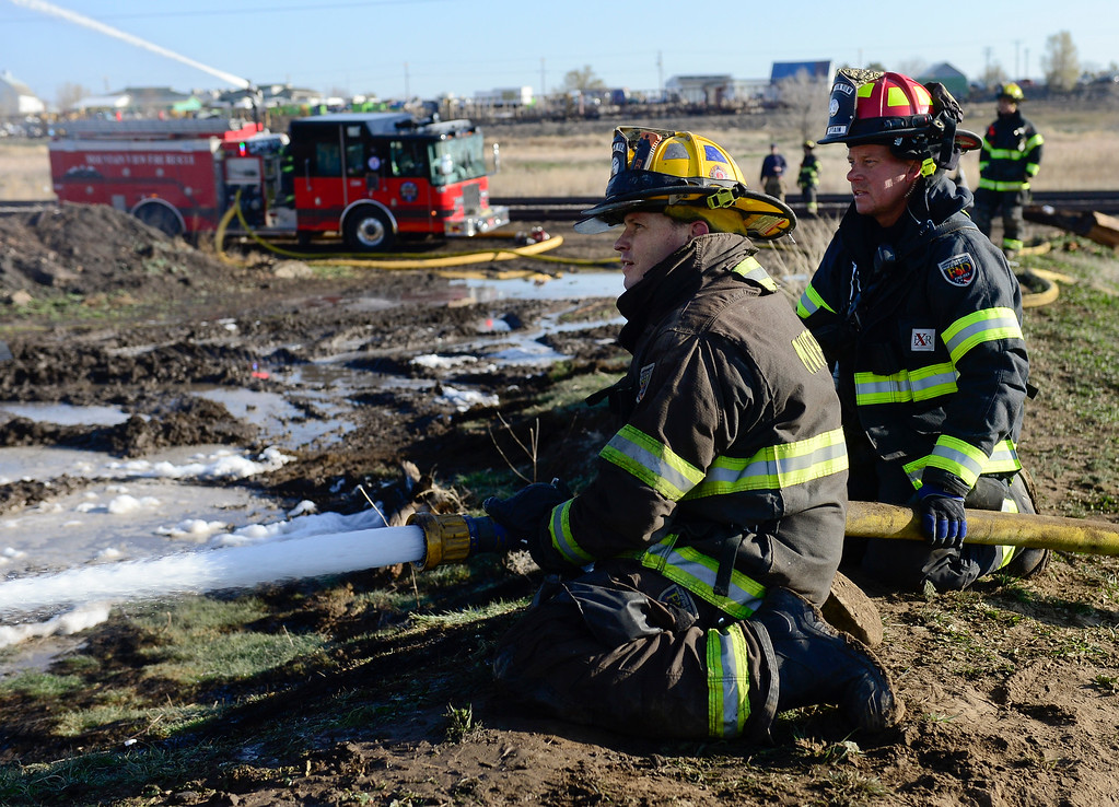 Description of . Mountain View Fire Rescue fire medic Danny Johnson, left, and captain Randy Chase pour water onto a hot spot at the scene of the railroad tie pile fire Thursday morning, April 17, 2014. (Lewis Geyer/Times-Call) TO VIEW A VIDEO AND SLIDESHOW VISIT WWW.TIMESCALL.COM