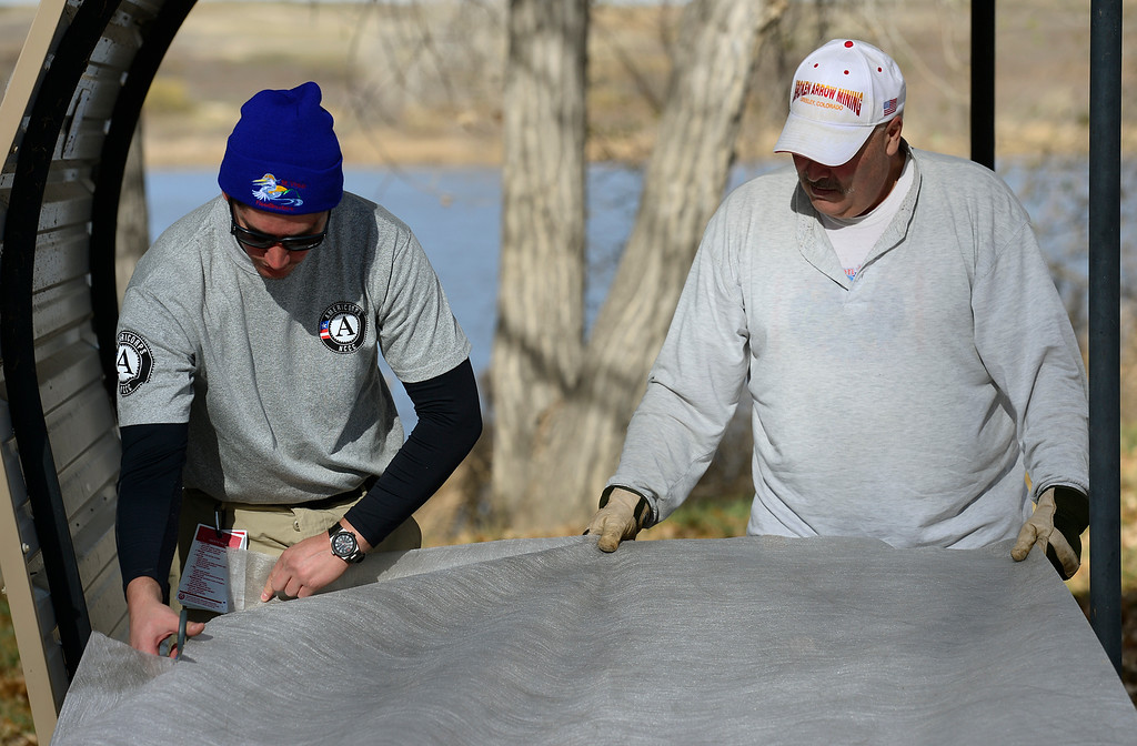 Description of . AmeriCorps member Ryan Miller, left, and volunteer Jeff Friesner, of Longmont, lay groundcover at a campsite during a cleanup day at St. Vrain State Park Saturday Nov. 16, 2013. (Lewis Geyer/Times-Call)