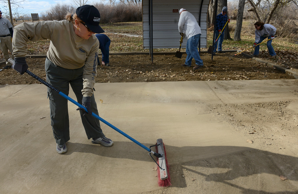 Description of . Yvonne Gilstrap, of Aurora, sweeps dirt from a concrete pad during a volunteer cleanup day at St. Vrain State Park Saturday Nov. 16, 2013. (Lewis Geyer/Times-Call)
