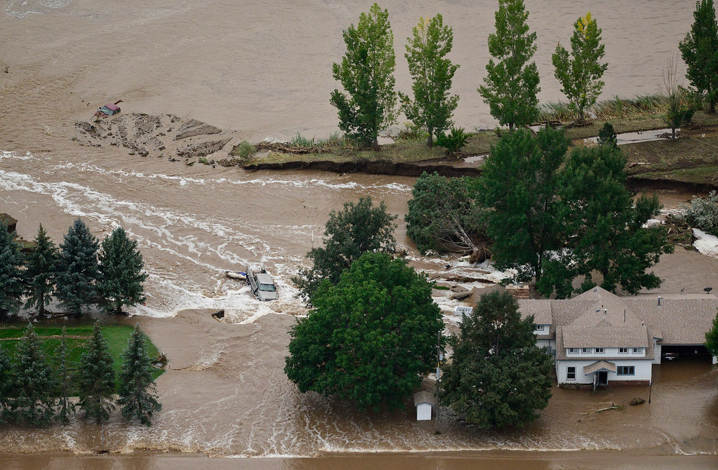 . A flooded house and vehicles submerged in flood water are seen, Saturday, Sept. 14, 2013, near Longmont. (Matthew Jonas/Times-Call)