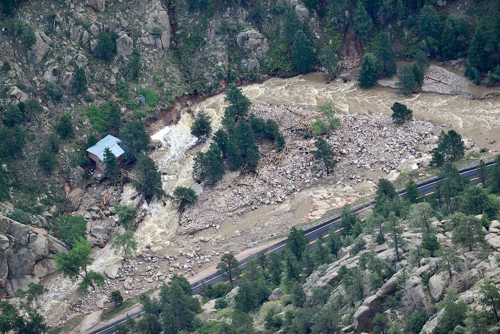 . A house that appears undamaged is seen next to South St. Vrain Creek, Saturday, Sept. 14, 2013, in Lyons. (Matthew Jonas/Times-Call)