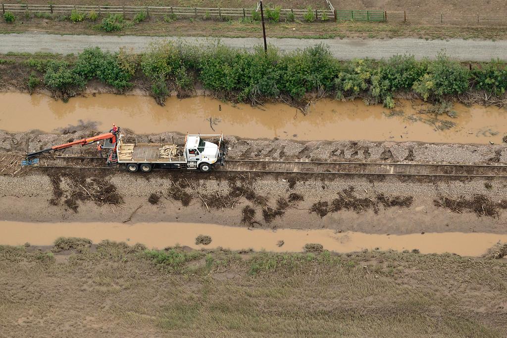 . Crews work to remove debris from railroad tracks near the Diagonal Highway, Saturday, Sept. 14, 2013, near Longmont. (Matthew Jonas/Times-Call)
