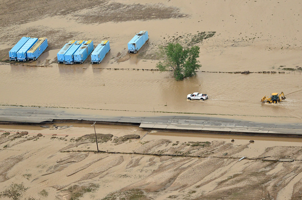 . A pickup truck and tractor are seen navigating the flood waters on Highway 119, Saturday, Sept. 14, 2013, outside Longmont. (Matthew Jonas/Times-Call)