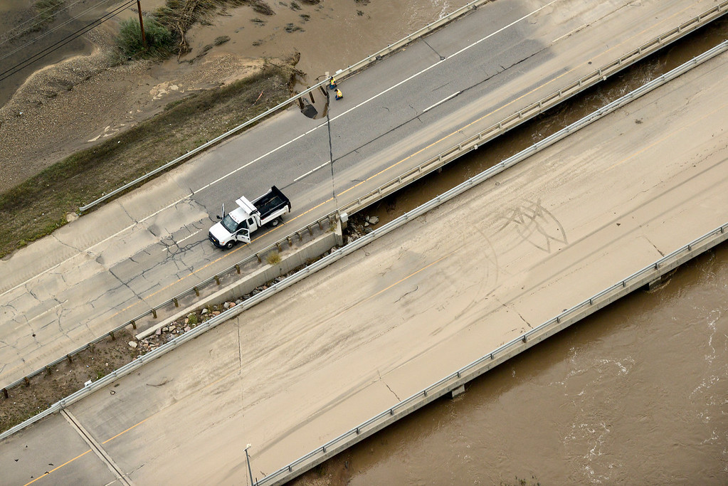 . Crews check out a hole through a bridge on Highway 119 east of Longmont, Saturday, Sept. 14, 2013. (Matthew Jonas/Times-Call)