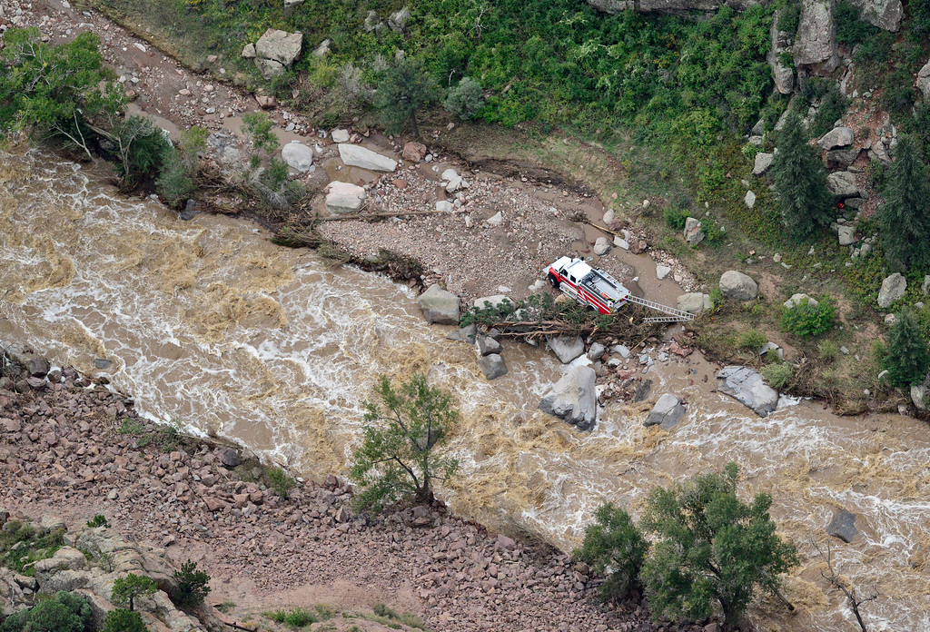 . A fire truck, which appears to be cut off from the road, is seen next to North St. Vrain Creek,  Saturday, Sept. 14, 2013, near Lyons. (Matthew Jonas/Times-Call)