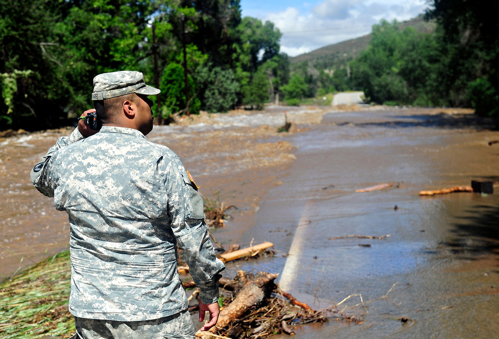 . Colo. National Guard Spec. Jose Alvarez inspects flood damage along Colo. Highway 36 north of Lyons Friday, Sept. 13, 2013. For more photos visit www.TimesCall.com. (Greg Lindstrom/Times-Call)