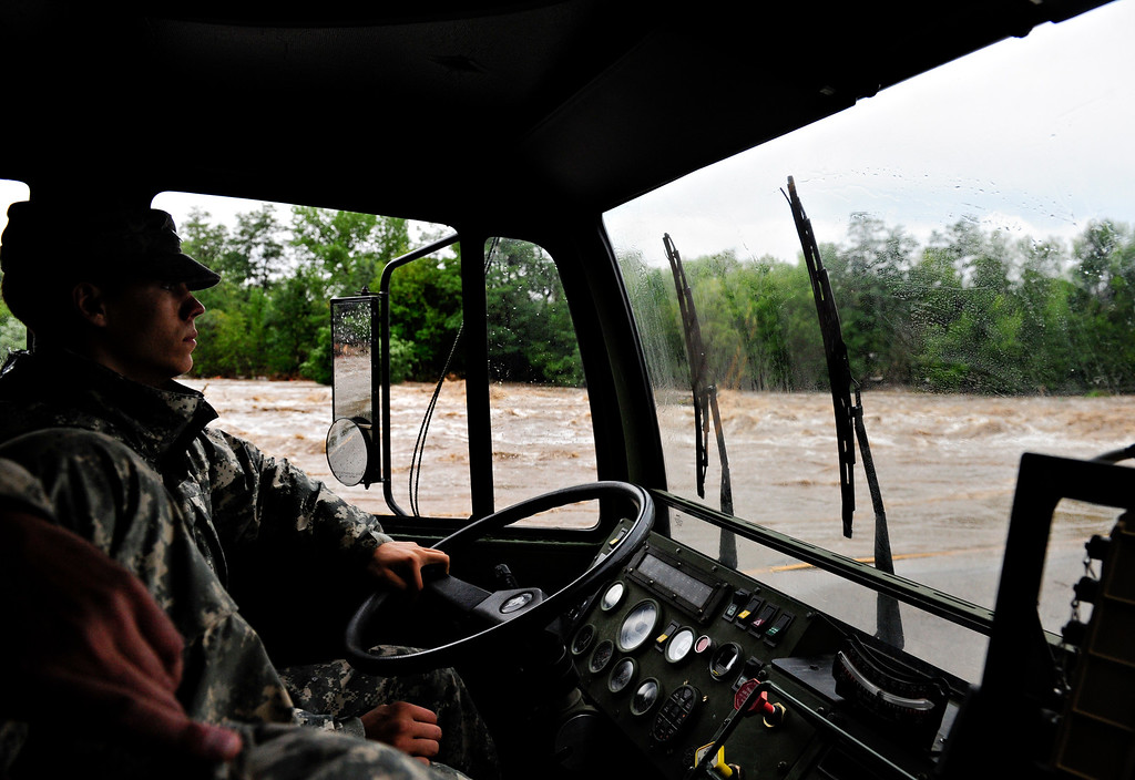 . Spc. Daniel Lapp, with the Colo. National Guard, drives along Colo. Highway 66 into Lyons as the St. Vrain River rages Friday, Sept. 13, 2013. (Greg Lindstrom/Times-Call)