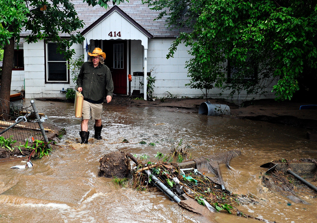 ". Gary McCrumb wades through flood waters as he carries valuables out of his home, 414 Park Dr., in Lyons Friday, Sept. 13, 2013. McCrumb is planning to stay with friends in town. ""We\'re all taking care of each other,\"" said McCrumb. For more photos visit www.TimesCall.com. (Greg Lindstrom/Times-Call)"