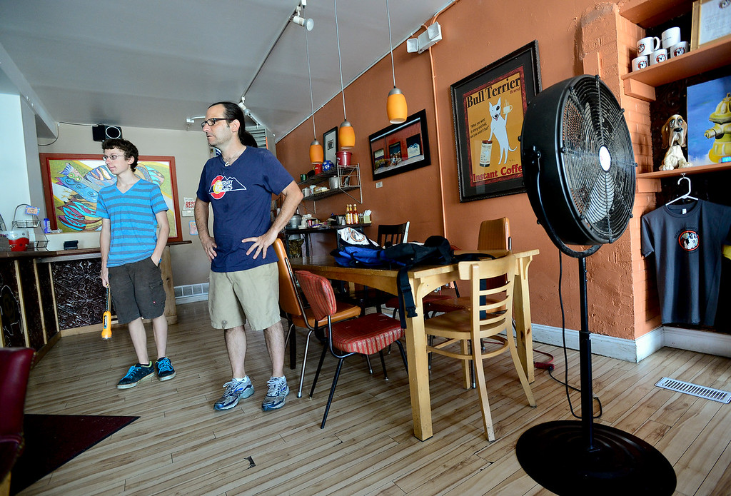 . From left: Landin Chesne, 15, and his father Greig Chesne, owner of Barking Dog Cafe, both of Longmont, try to decided what needs to be unplugged or thrown out before they leave the store, Wednesday, Sept. 18, 2013, in Lyons. The town has been without power since early Thursday, Sept. 12. (Matthew Jonas/Times-Call)