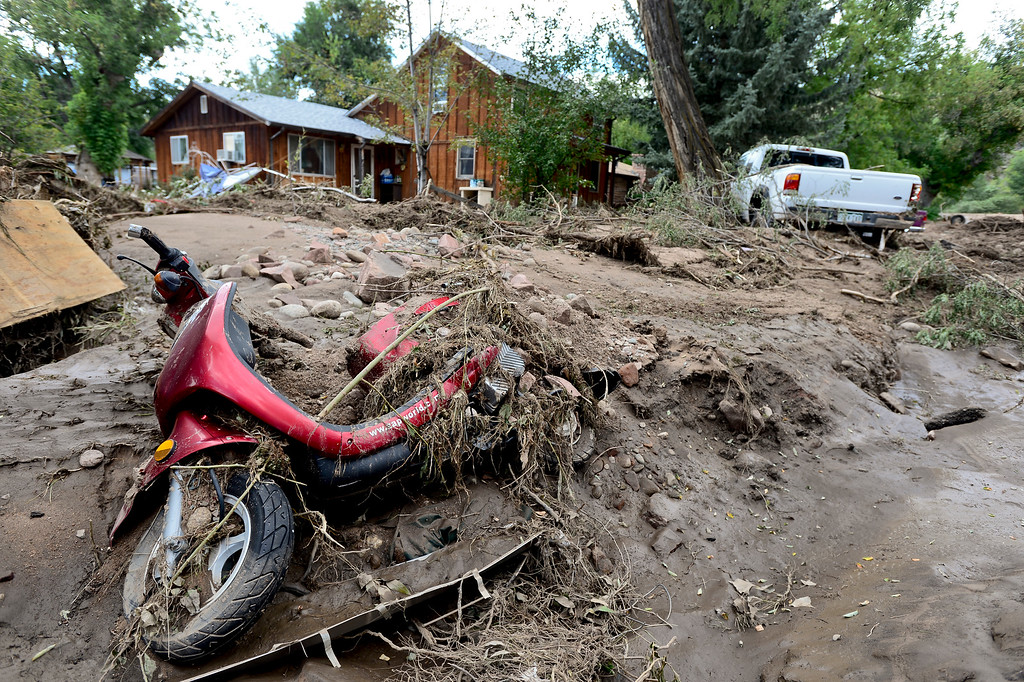 . A scooter is seen partially submerged in mud on Evans Street, Wednesday, Sept. 18, 2013, in Lyons. (Matthew Jonas/Times-Call)