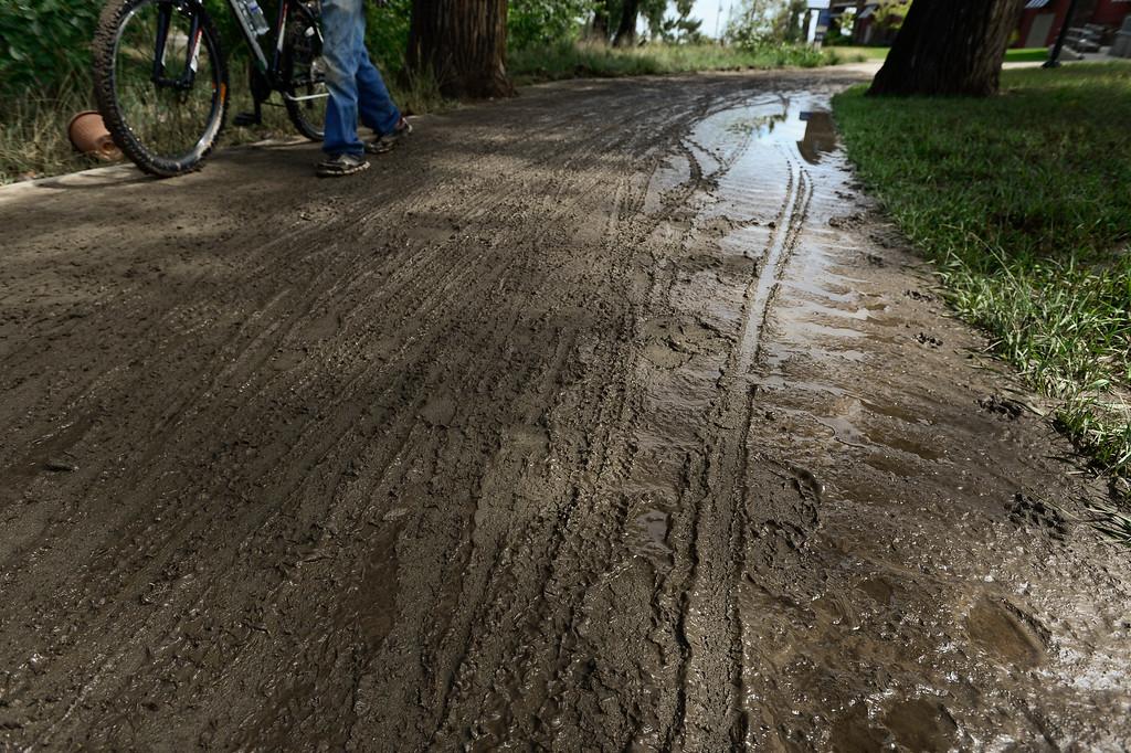 . A man walks his bicycle through the mud on the St. Vrain Greenway path near Ken Pratt and Martin Street, Friday, Sept. 13, 2013, in Longmont. (Matthew Jonas/Times-Call)