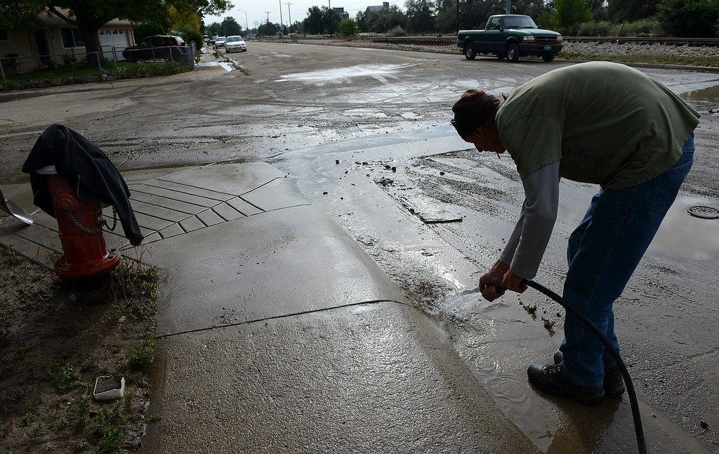 . Val Shockey hoses mud off the street on First Avenue in the Bohn Park neighborhood, Saturday morning, Sept. 14, 2013. (Lewis Geyer/Times-Call)