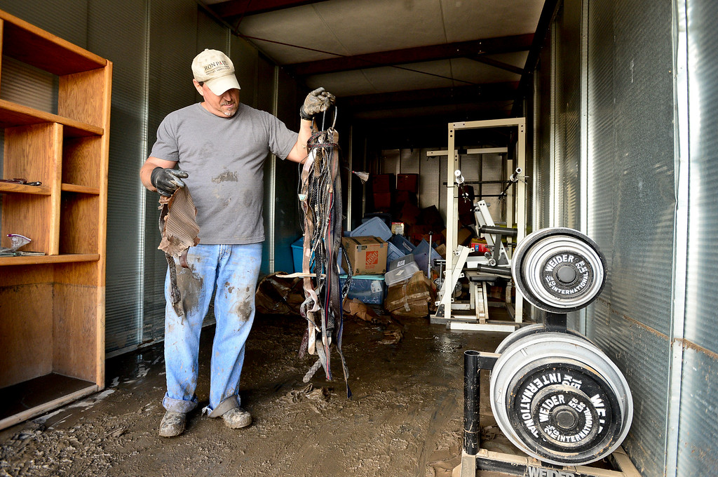 . Ron Genova, of Spring Gulch, a subdivision near Lyons, takes a look at belts and bolo ties he pulled from his flood damaged belongings in a storage unit, Monday, Sept. 23, 2013, at Storage West Self Storage in Longmont. (Matthew Jonas/Times-Call)