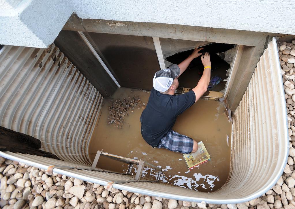 . Tyler Shmorr photographs flood damage in a home in the Champion neighborhood in Longmont, Colorado, on September 14, 2013. Cliff Grassmick / September 14, 2013