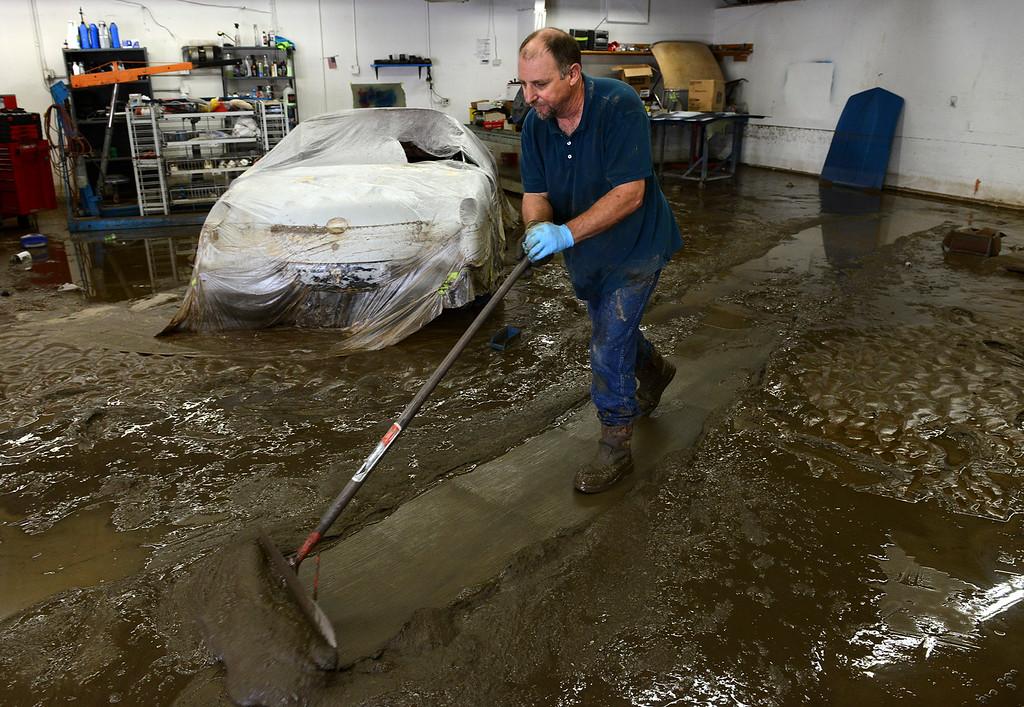 . Curt Ingram, owner of Corvett Spa & Motorsports, 100 S. Bowen Cir., pushes mud out of his garage Monday morning, Sept. 16, 2013. (Lewis Geyer/Times-Call)