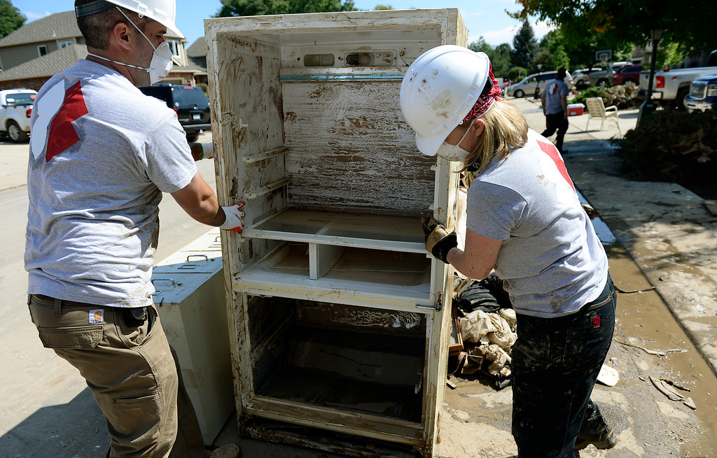 . Team Rubicon volunteers Nick Lascanic and Dana Niemela help move a refrigerator to the curb for disposal in The Greens neighborhood Thursday, Sept. 19, 2013. (Lewis Geyer/Times-Call)