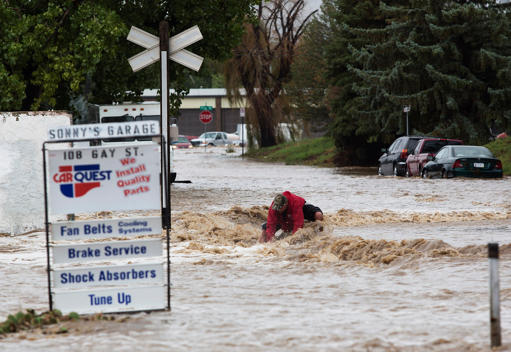 . A man fights against the current on the railroad tracks near 1st and Gay St. as the St. Vrain river floods after days of torrential rains, on Thursday Sept. 12, 2013 in Longmont, Colo. (Photo by Eric Bellamy/Times-Call)