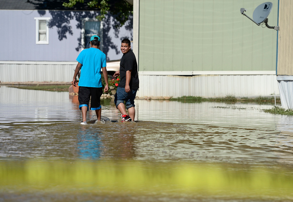 . Two unidentified people walk through the flood water in the River Valley Village mobile home park, Tuesday, Sept. 17, 2013, in Del Camino. (Matthew Jonas/Times-Call)