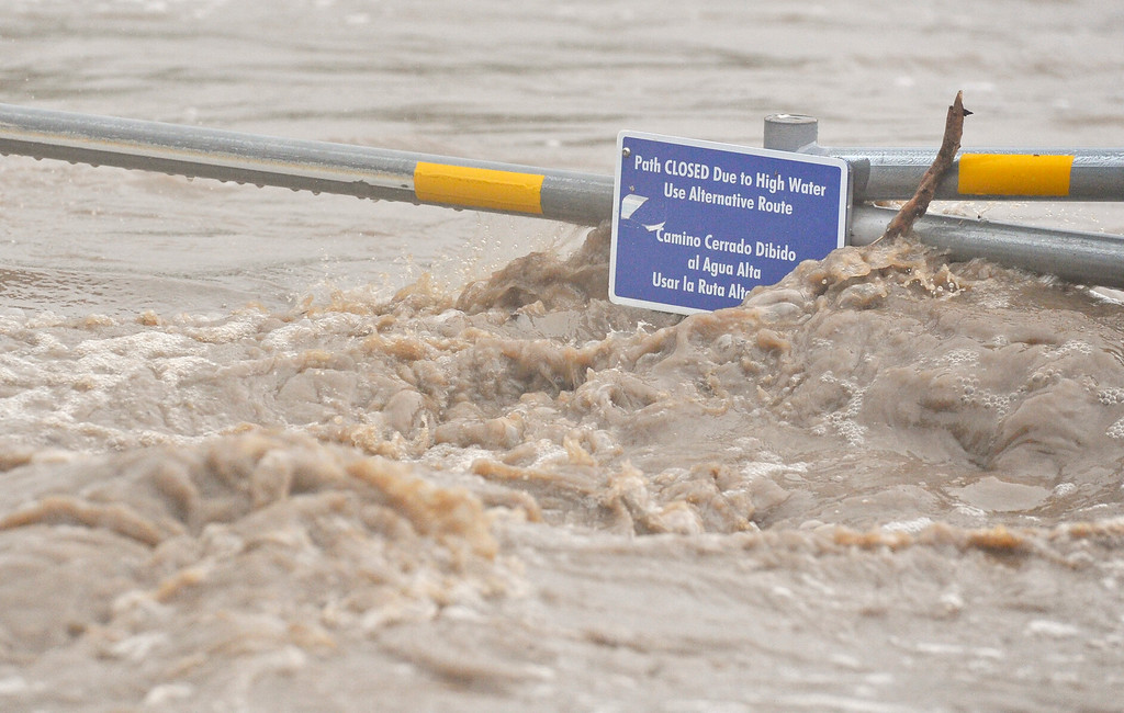 . A sign posted to a barricade is nearly submerged by the St. Vrain River, Thursday, Sept. 12, 2013, in Longmont. (Matthew Jonas/Times-Call)