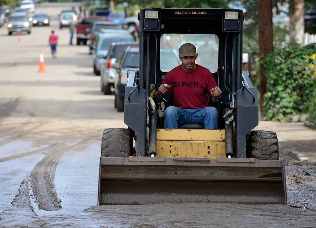 . Landscaper Bryan Dugan volunteers his time and his skidsteer to clear mud off the 100 block of Bowen Street, in the Bohn Park neighborhood, Saturday morning, Sept. 14, 2013. (Lewis Geyer/Times-Call)