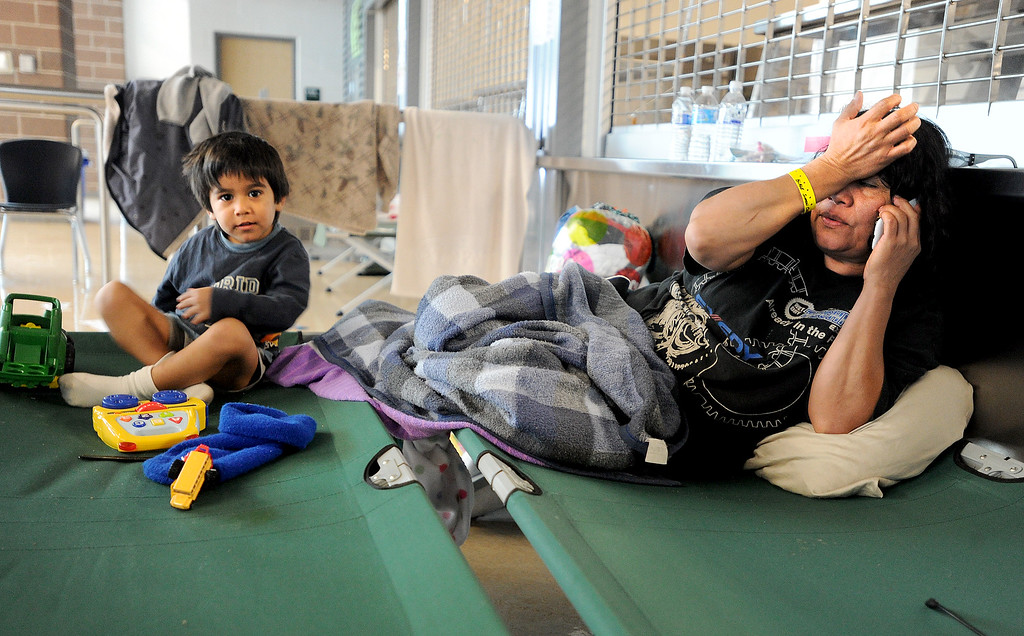 . Carlos Duron, 3, plays on a cot, while his mother, Vilma Maldonado, talks on the phone in Mead, Colorado on September 15, 2013. Both are evacuees from Longmont staying at Mead High School with the Red Cross.  Cliff Grassmick / September 15, 2013