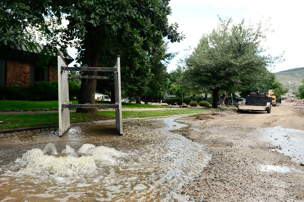 . Raw sewage spews from a cover, Monday, Sept. 16, 2013, in Lyons. (Matthew Jonas/Times-Call)
