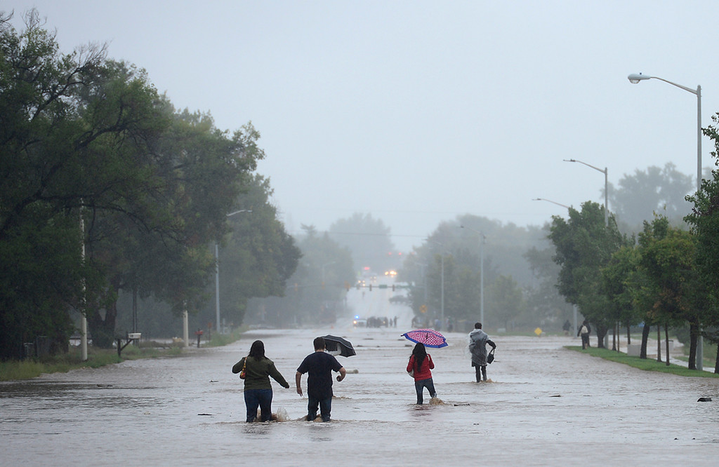 . Longmont residents trying to get the north side of the city walk north on a flooded Hover Street Thursday Sept. 12, 2013. (Lewis Geyer/Times-Call)