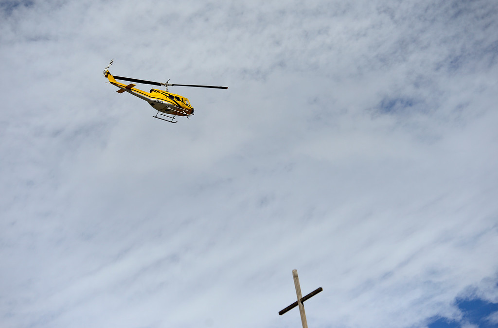 . A helicopter flies over a cross on top of Lyons Community Church, Wednesday, Sept. 18, 2013, in Lyons. (Matthew Jonas/Times-Call)
