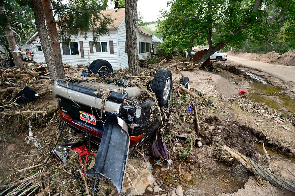 . A destroyed Subaru covered in debris is seen sitting upside down in the front yard of a home at the corner of 4th Avenue and Evans Street, Wednesday, Sept. 18, 2013, in Lyons. (Matthew Jonas/Times-Call)