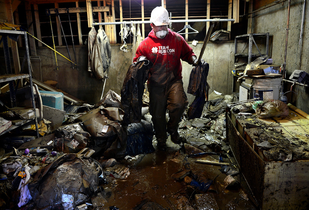 . Team Rubicon volunteer Christian Somoza removes debris Thursday, Sept. 19, 2013 from a basement that had been flooded in The Greens neighborhood. (Lewis Geyer/Times-Call)