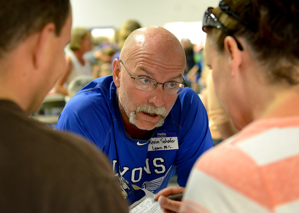. Lyons sixth grade math and science teacher Kevin Schafer helps parents during a gathering of Lyons-area school students and their families at Calvary Church, 2101 Gay St., Monday afternoon, Sept. 16, 2013. (Lewis Geyer/Times-Call)