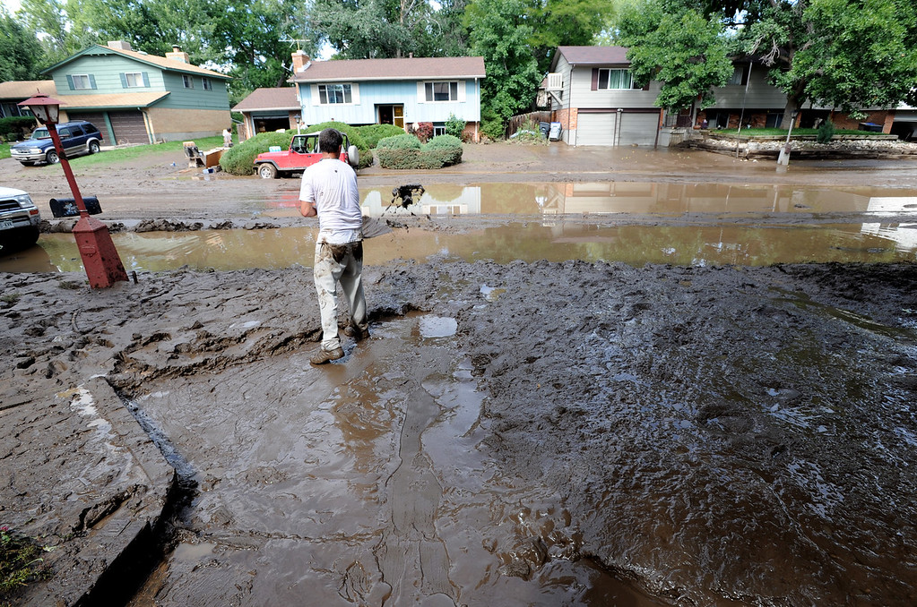 . Longmont Flood Damage Day 3 270.JPG Mark Swanson shovels out the mud from this home on Lefthand Drive in Longmont, Colorado, on September 14, 2013. Cliff Grassmick / September 14, 2013