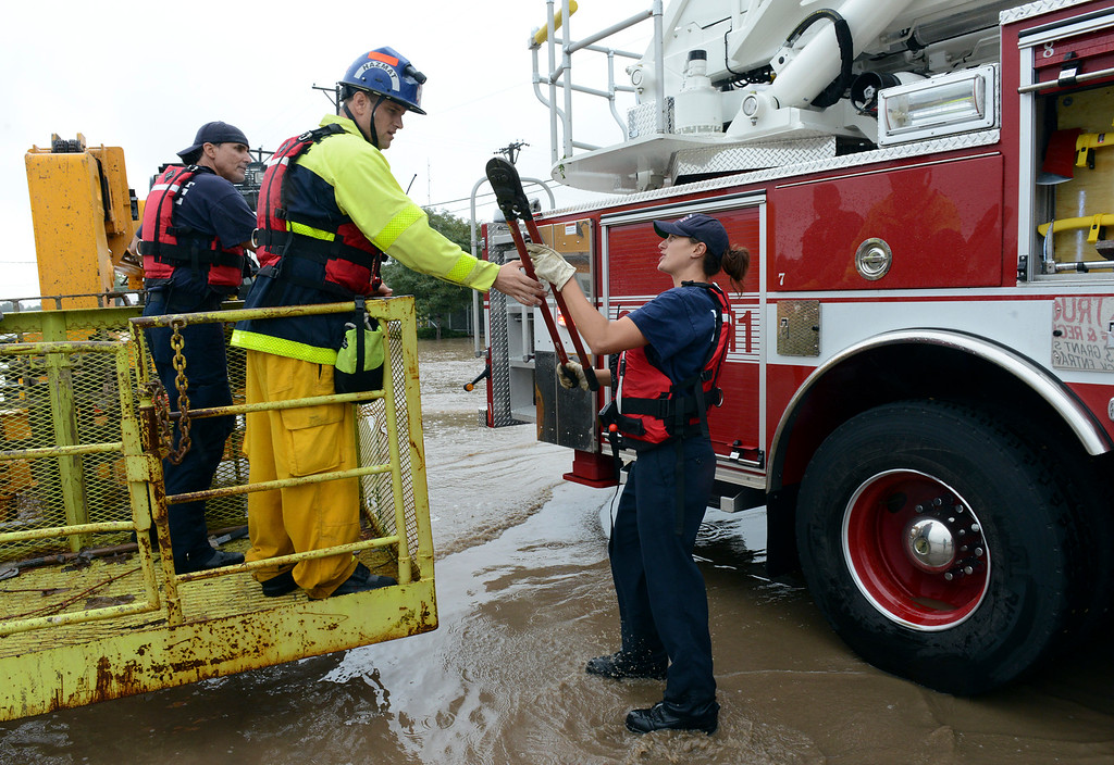 . Longmont firefighters gather tools for a rescue operation on Boston Avenue Thursday, Sept. 12, 2013. (Lewis Geyer/Times-Call)