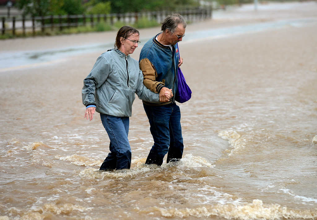 . Cathy and Danny Hirsch make their way across a flooded Boston Avenue at Hover Street Thursday Sept. 12, 2013. (Lewis Geyer/Times-Call)