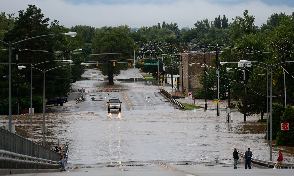 . Water flows across S. Pratt Parkway, looking south from the bridge over the railroad tracks, 7 a.m. Friday, Sept. 13, 2013. (Lewis Geyer/Times-Call)