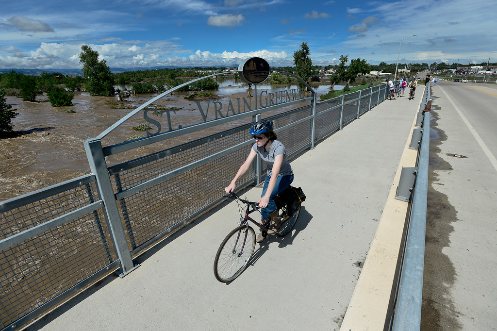 . A woman on a bicycle crosses the Martin Street Bridge over the flooded St. Vrain River, Friday, Sept. 13, 2013, in Longmont. (Matthew Jonas/Times-Call)