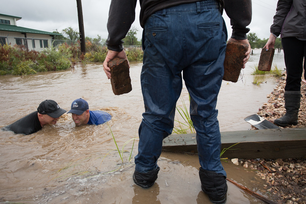 . A group of residents work to plug a culvert under the train tracks near Sunset St. in a vain attempt to stem the flow as the St. Vrain river floods after days of torrential rains, on Thursday Sept. 12, 2013 in Longmont, Colo. (Photo by Eric Bellamy/Times-Call)
