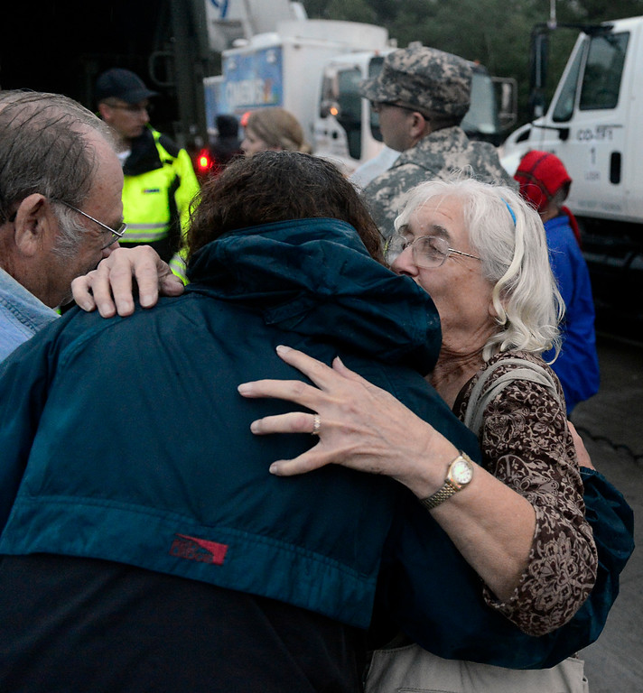 . June Stacy, right, and her husband Charles embrace their old friend Ellen Rosenberg Thursday, Sept. 12, 2013, after being transported from Lyons. The Colo. National Guard Civil Support Team entered Lyons on Thursday afternoon, Sept. 12, 2013, with three 2.5-ton LMTV trucks carrying supplies and crews, according to Maj. Gordon Hunter. For more photos visit www.TimesCall.com. (Greg Lindstrom/Times-Call)